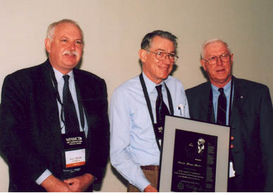 Harold Reiter (centre) receives his Paul Erdös Award from WFNMC President Peter Taylor (left) and WFNMC Awards Committee Chairman Ron Dunkley (right). The presentation took place on Saturday 10 August 2002, at the Ibis Hotel, Melbourne, as part of WFNMC's 4th conference.